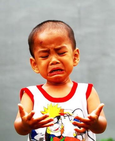 Bébé pleure parce qu'il a les mains sales